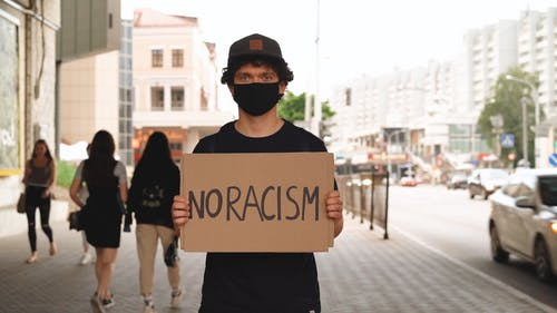 Young Man On Sidewalk Holding A Placard Of No Racism