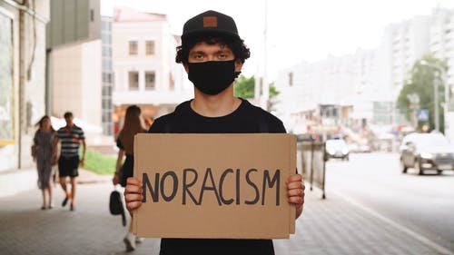 Man Standing On Sidewalk With Placard Of No Racism