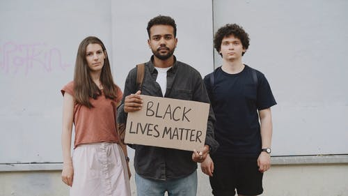 Man And Woman Standing Beside A Man Holding A Placard With Black Lives Matter Text