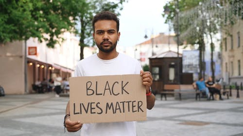 Man Holding A Placard With Black Lives Matter Text