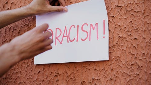Person Holding A No Racism Sign On Rough Wall