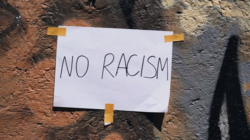 White Paper With No Racism Text Taped On A Rock