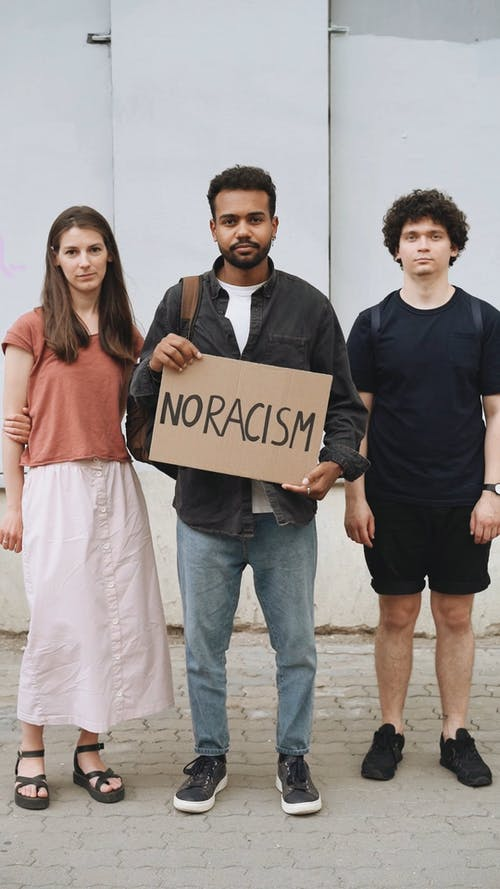 Man Holding A Placard On No Racism