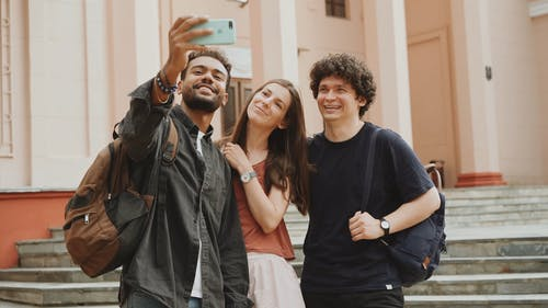 Two Men And A Woman Grouping Together For A Selfie Photo