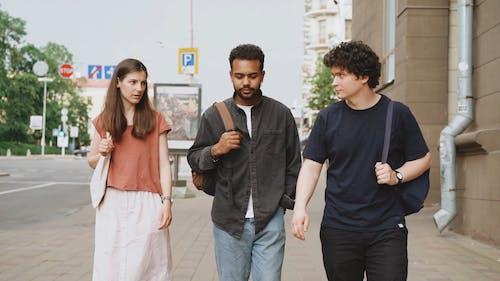 People Having Conversation While Walking On Sidewalk
