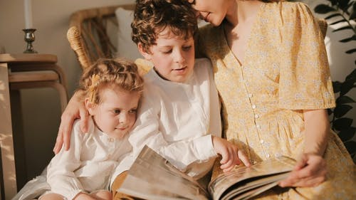 A Mother Reading A Book With Childer