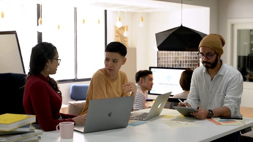 A Group Of People Working Together Inside An Office