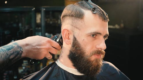 A Barber Using An Electric Shaver To Cut The Hair Of A Man