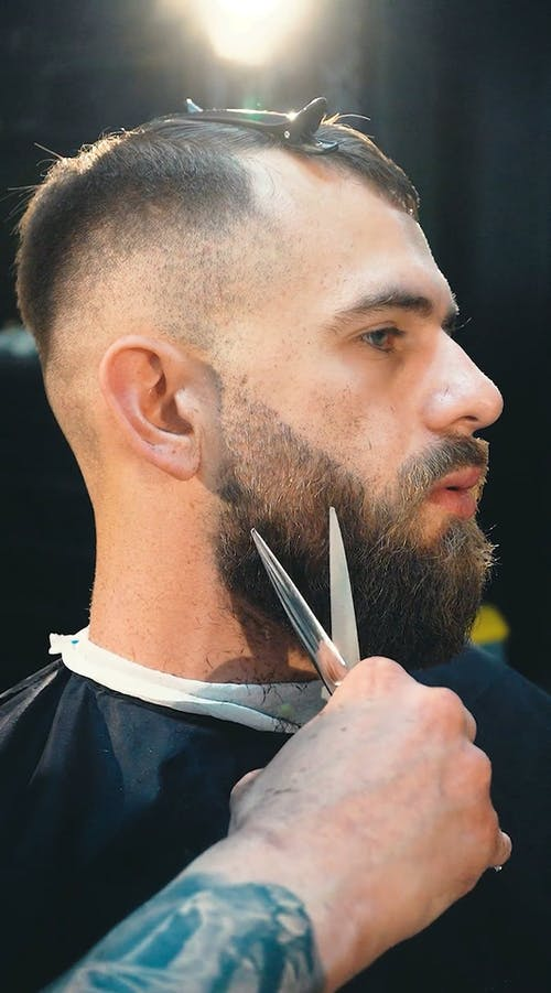 A Man Trimming The Beard Of His Customer