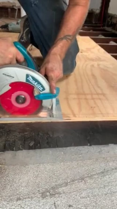 Person Cutting Wooden Board With A Circular Saw