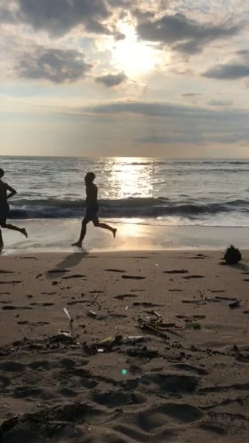 Two Persons Running Along The Seashore