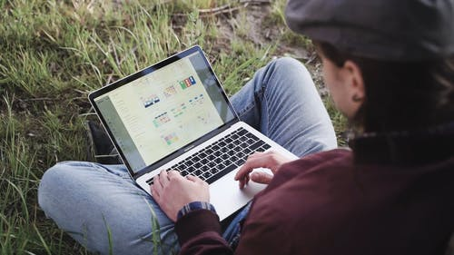 Man Sitting On Grass Using A Laptop