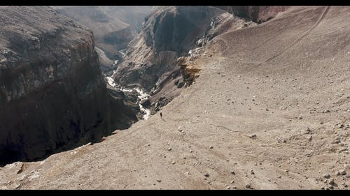 An Aerial Footage of a Person Walking on the Edge of a Cliff