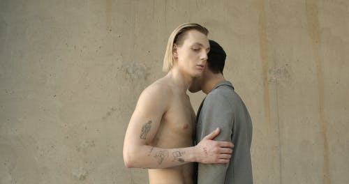 Shirtless Man Holding Another Man In Gray Coat