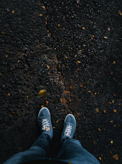 Person Standing On Asphalt Ground With Leaves Falling