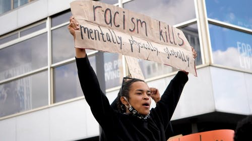 Woman Holding a Protest Sign on the Street