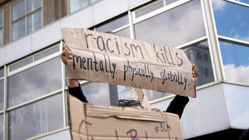 Woman Holding a Protest Cardboard on the Street