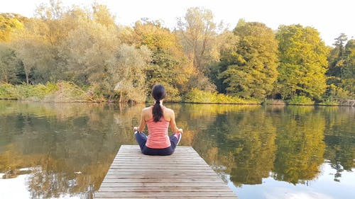 Video Of Woman Meditating On Wooden Dock