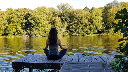 Woman Sitting On The Dock In A Yoga Position