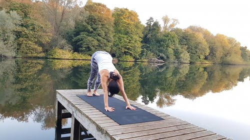 Video Of Woman Doing Stretching Exercises On Wooden Dock