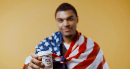 Man With an American Flag Holding a Paper Cup