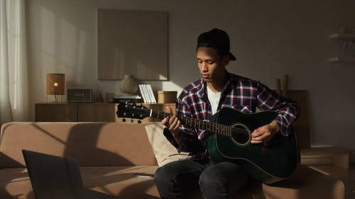 Video Of Man Playing Acoustic Guitar While Sitting On Sofa
