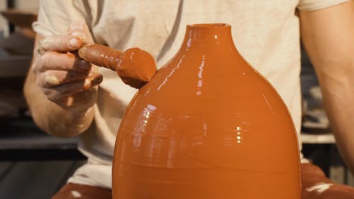 Video Of Man Putting Color On Clay Pot