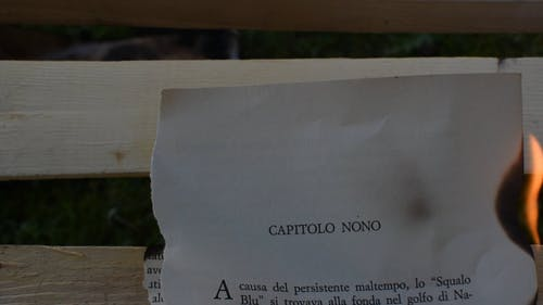 A Burning Page Of A Book On Wooden Surface