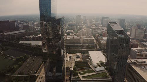 Drone Footage of a Tall Glass Building in the City