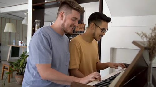Gay Couple Playing The Piano Together
