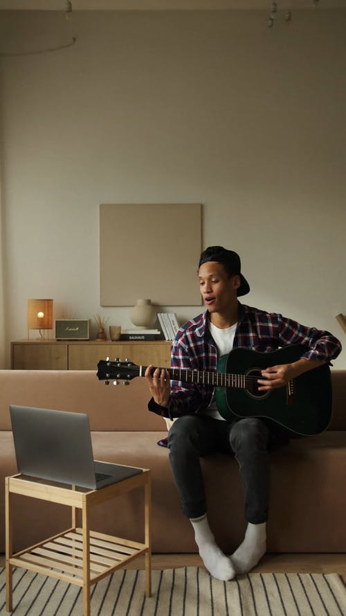 Man Singing And  Playing The Guitar At Home