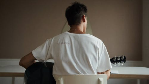 Back View of Man in White Shirt Playing an Acoustic Guitar