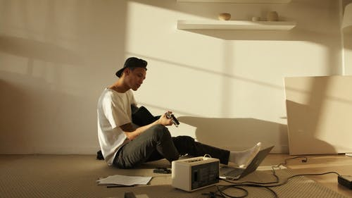 Man Playing Guitar In An Empty Room