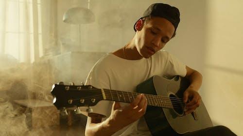 Man Tuning The Guitar