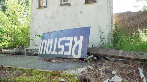 An Abandoned Building With A Broken Signboard Near The Wall
