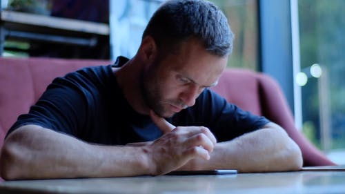 Man in Black Shirt Looking at His Smartphone