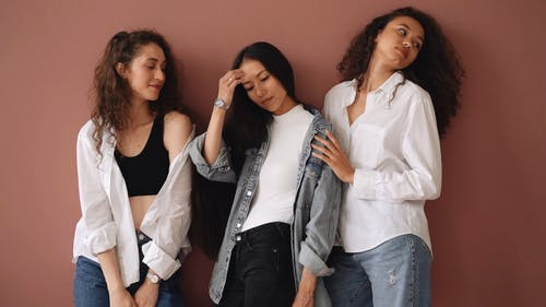 Portrait Of Three Women Posing And Wearing White Top