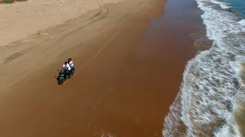 People On A Motorbike Driving Along The Seashore