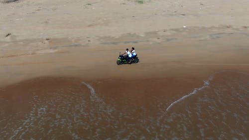 People On A Motorbike Driving Along The Shore