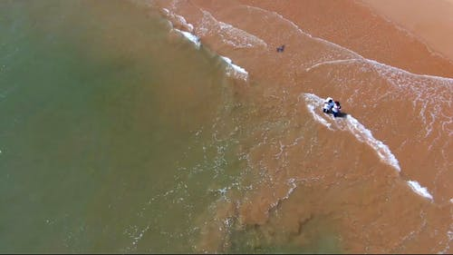 Drone Footage of Two Person Standing on Beach Shore