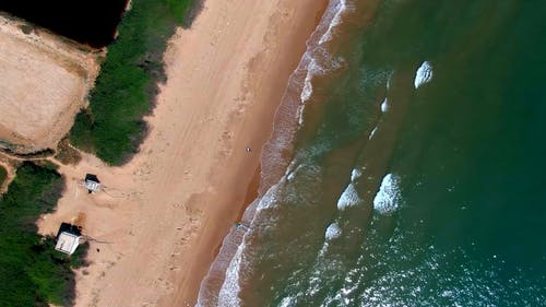 An Aerial Footage of Waves Crashing on the Seashore