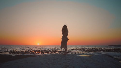 Silhouette Of A Woman Standing By The Shore