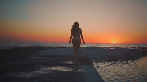 Silhouette Of A Woman Looking At The Sunset
