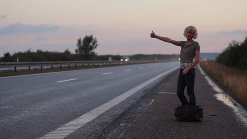 Woman Standing on Roadside Hitchhiking for a Ride