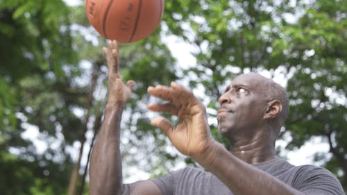 Man Spinning the Basketball on His Middle Finger