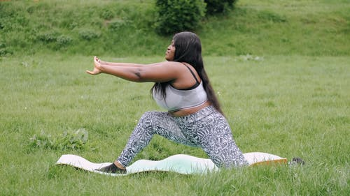 A Woman Doing Stretch Exercises Outdoors