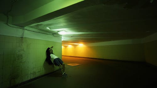 A Woman Leaning On The Underpass Wall