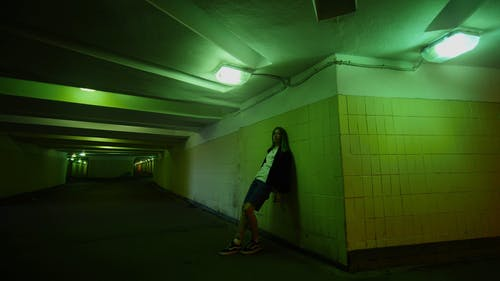 A Young Woman Leans On The Underpass Wall