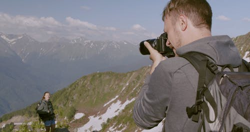 Man Taking Photo Of A Woman With View Of The Mountains On Background