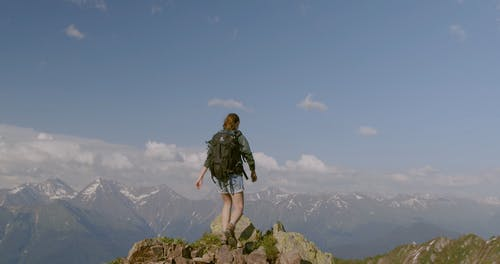 Woman Standing At The Peak Of A Rocky Mountain